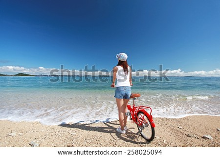 Young woman with a bicycle on the beach - stock photo