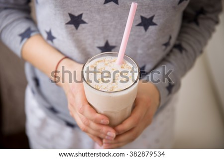 Young woman with a big glass of healthy smoothie served with a straw and oats. Hands holding milkshake. Stars background. Dairy snack or breakfast. Horizontal view. - stock photo