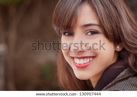 Young woman with a big smile looking at the camera on a brown coffee background