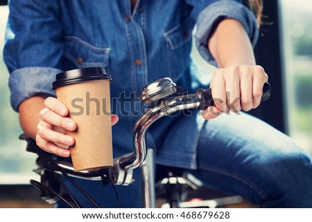 Young woman with a bike holds disposable brown paper cup of coffee. Copy space on cup.