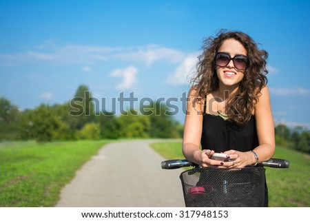 Young woman with a bike smiling and holding mobile phone in a summer park.