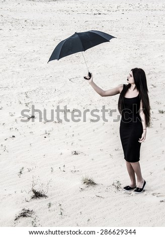 Young woman with a black umbrella in a dry desert