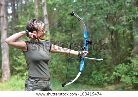young woman with a bow and arrows in the woods - stock photo