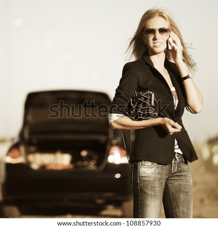 Young woman with a broken car calling for help - stock photo