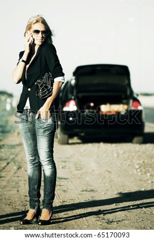 Young woman with a broken car calling for help. - stock photo