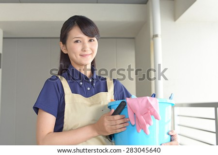 young woman with a broom sweeping the entrance.  - stock photo