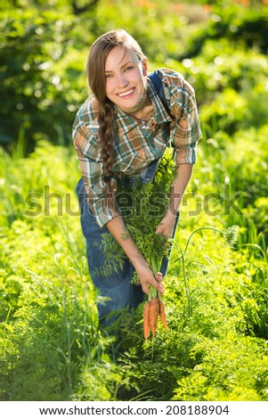 Young woman with a bunch of carrots in the garden - stock photo