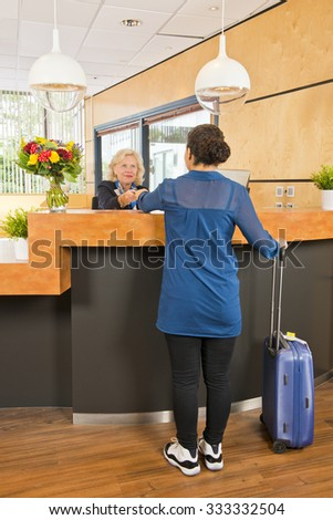 young woman, with a carry on suitcase next to her, handing over her passport, registering, during checkin at a hotel, where a senior receptionist provides customer service - stock photo