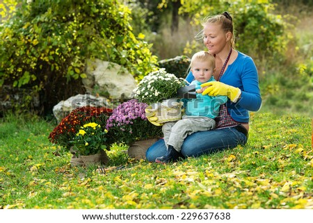 Young woman with a child are planting flowers in the garden