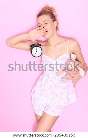 young woman with a clock in his hand. Yawning