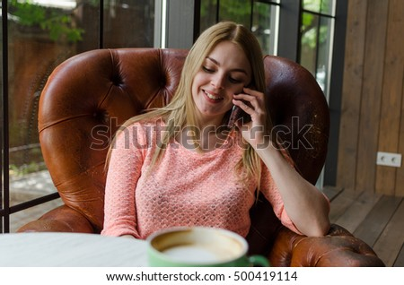 Young woman with a coffee and her cell phone