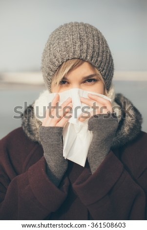 Young woman with a cold holding a tissue