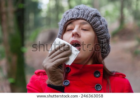 Young woman with a cold or flu sneezing on a white paper handkerchief on a forest wearing a red overcoat, a beanie and gloves during winter  - stock photo