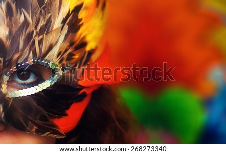 Young woman with a colorful feather carnival face mask on bright colorful background, eye contact, make up artist - stock photo