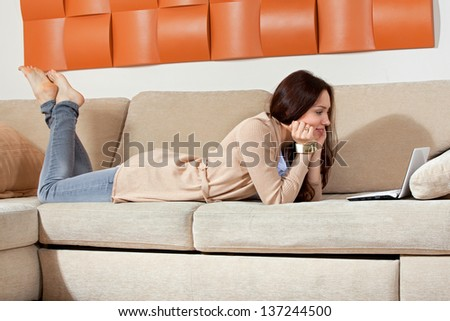 Young woman with a computer is lying on the sofa
