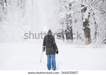 Young woman with a crutch, in the park, enjoying the snow falling