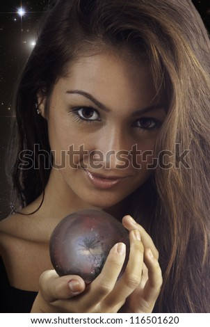 young woman with a crystal ball with a tropical scene inside - stock photo