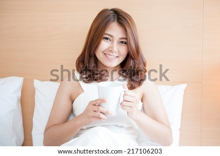 young woman with a cup of coffee on the bed