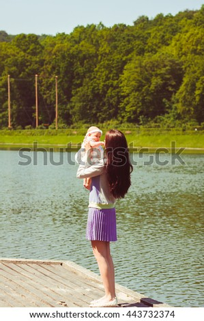 Young woman with a daughter on the lake