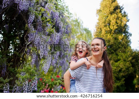 Young woman with a daughter walk in the garden. Couple surrounded by beautiful vegetation. The faces of the joy of communicating with nature. Concern about the health and development of the child