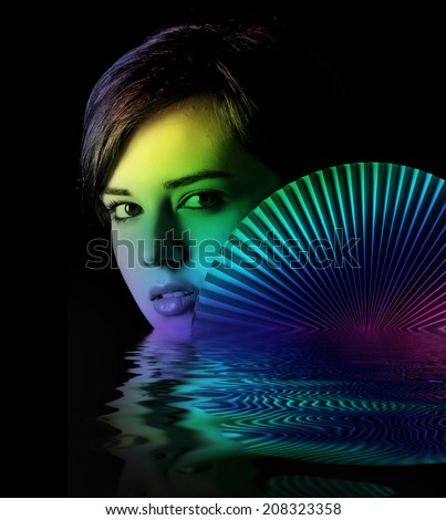 young woman with a fan on dark background