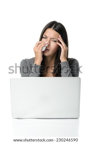 Young woman with a fever and chills from seasonal influenza holding a tissue to her streaming nose and a hand to her forehead as she winces in pain from a headache - stock photo