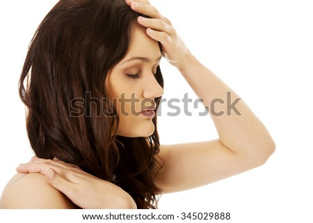Young woman with a fever touching her forehead.