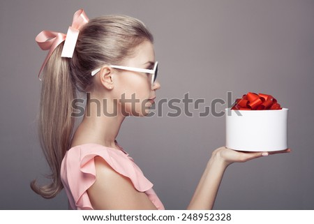 Young woman with a gift in hand. - stock photo