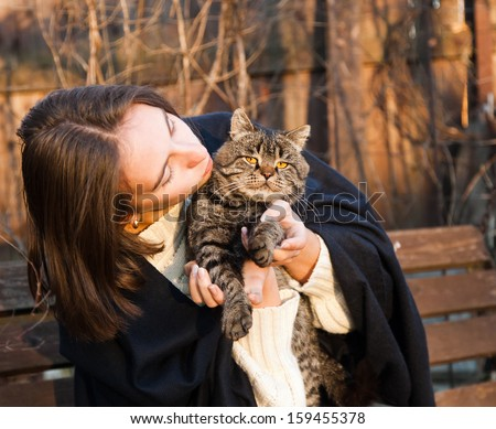 young woman with a gray striped cat - stock photo