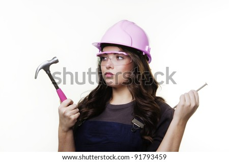 young woman with a hard hat and hammer getting ready to do some DIY - stock photo
