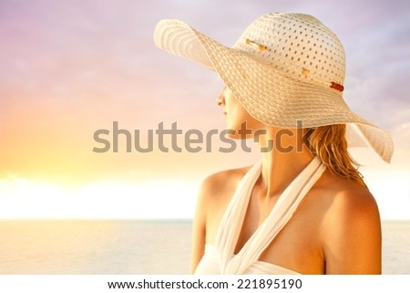 Young woman with a hat enjoying summer at the beach. - stock photo