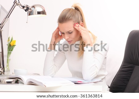 Young woman with a headache working on the computer.