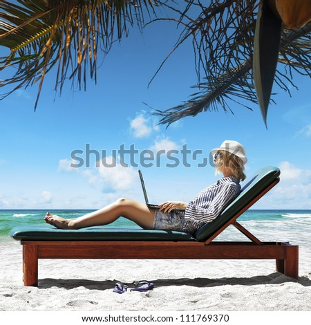 Young woman with a laptop under the palm tree - stock photo