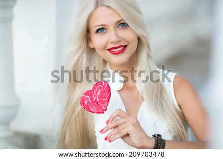 Young woman with a lollipop. Cheerful girl in sunglasses and a knitted hat have fun with candy in her hands. Licking candy. Outdoors, lifestyle. Elegant blonde woman with lollipop in heart shaped - stock photo