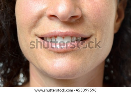 Young woman with a lovely sensual smile and slightly parted lips showing her teeth, close up detail of her mouth