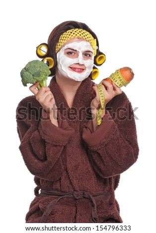 Young woman with a mask on her face holds broccoli and carrot isolated over white background