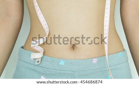 young woman with a measuring tape - stock photo