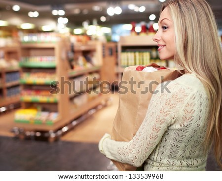 Young woman with a package of products in a store