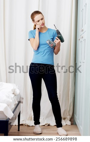 Young woman with a power drill - stock photo