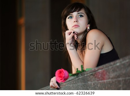 Young woman with a red rose. - stock photo