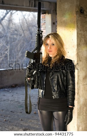 Young woman with a rifle in abandoned house - stock photo