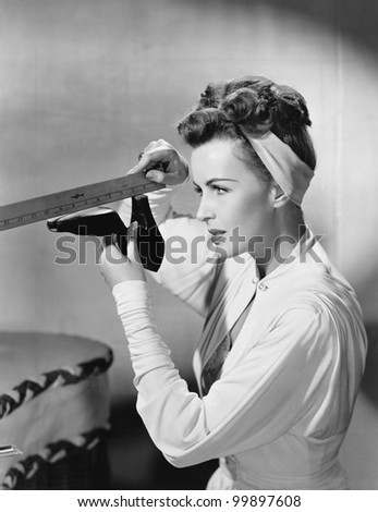 Young woman with a ruler measuring her shoe - stock photo