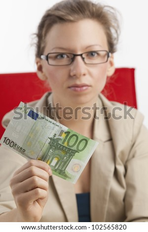 Young woman with a serious look is holding a hundred euro note - stock photo