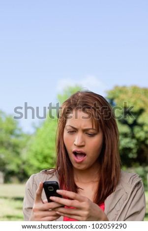 Young woman with a shocked expression on her face while reading a text message in a sunny park area - stock photo