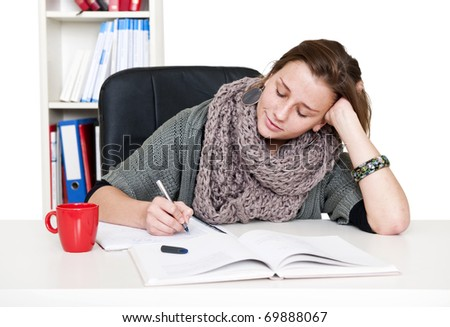 Young woman with a smile on her face taking notes from a textbook