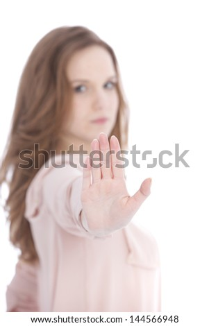 Young woman with a stern expression giving a Stop gesture with her hand holding up the palm facing the camera to indicate she has had enough - stock photo