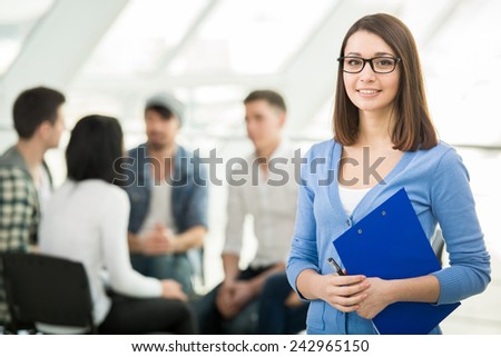 Young woman with a tablet and a group of people in the background. - stock photo
