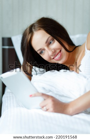 Young woman with a tablet pc in her hands lying in a bed and looking on a screen - stock photo