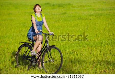 Young woman with a vintage bicycle relaxing on a green meadow - stock photo