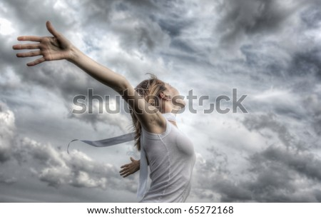 Young woman with a white ribbon and raised hands on clouds background